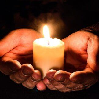 Hände halten eine Kerze